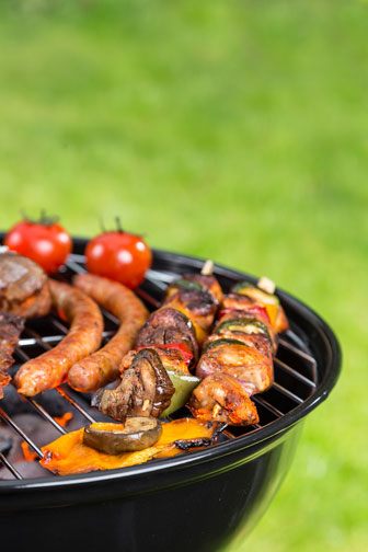 grilling various meats and tomatoes on a kettle barbecue grill