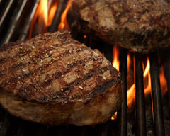 steaks cooking on a barbecue grill